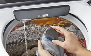 Person scrubbing a garment over a Whirlpool® Top Load Washing Machine with Built-In Faucet.