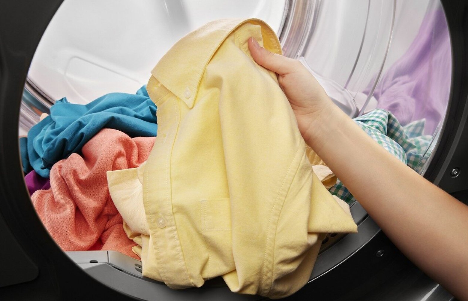 Hand pulling yellow shirt out of a dryer