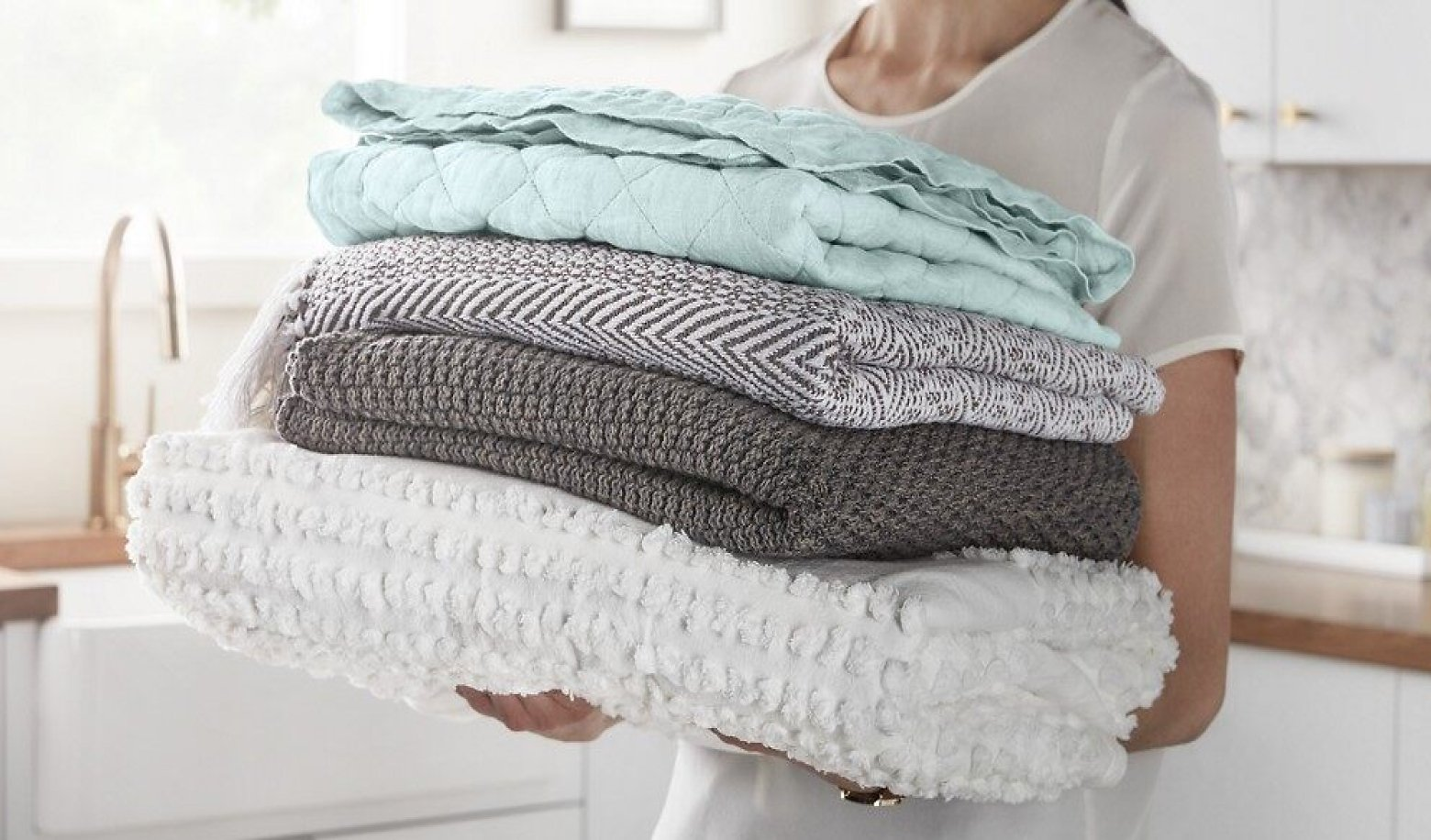 Woman carrying a stack of folded blankets