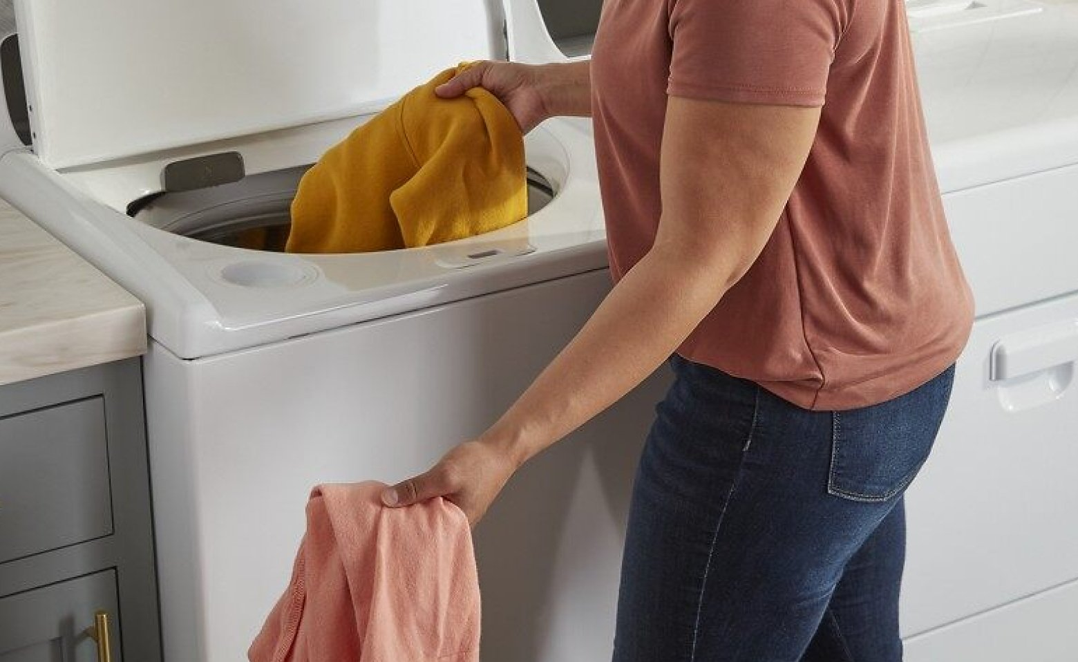 Person loading a washing machine with laundry