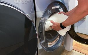 Man putting pillow into a washing machine