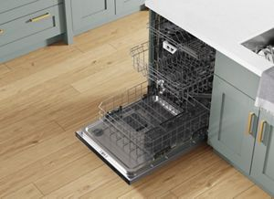 Angled overhead view of an open dishwasher with racks pulled out in a green kitchen