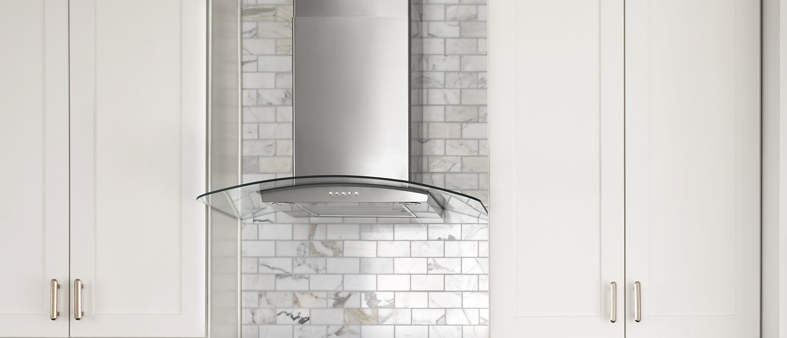 Glass-edged wall-mounted canopy hood between cabinets