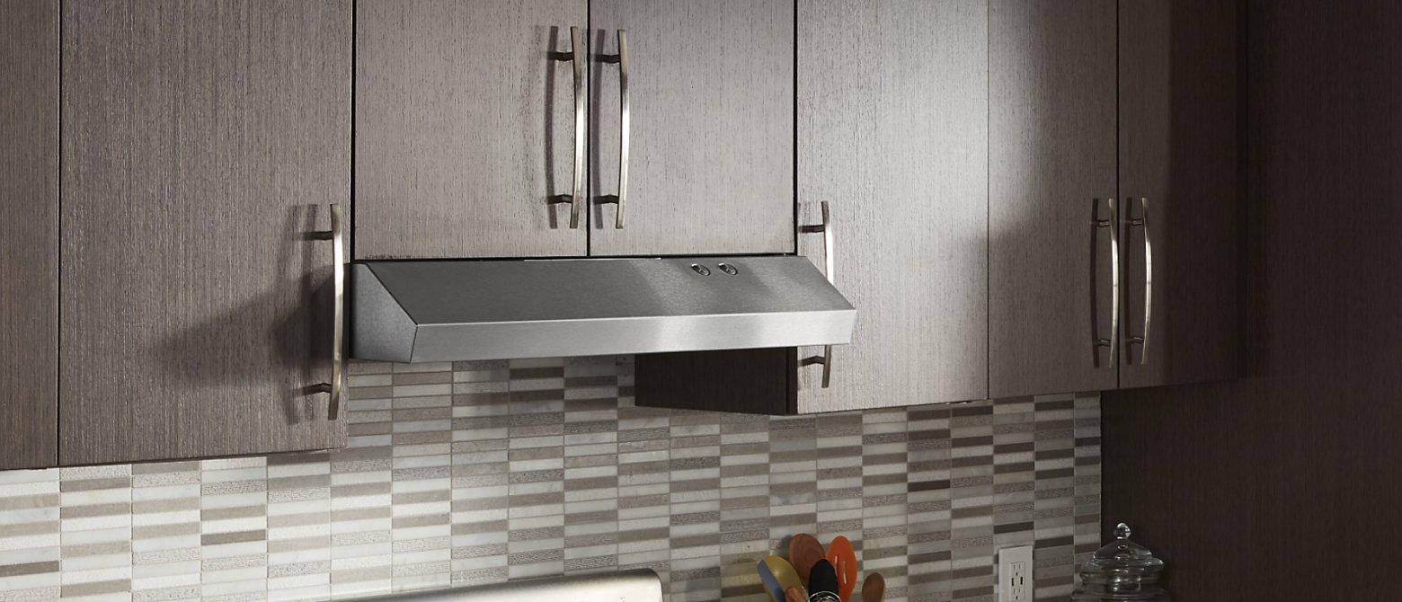 Undercabinet hood installed beneath modern wood cabinets