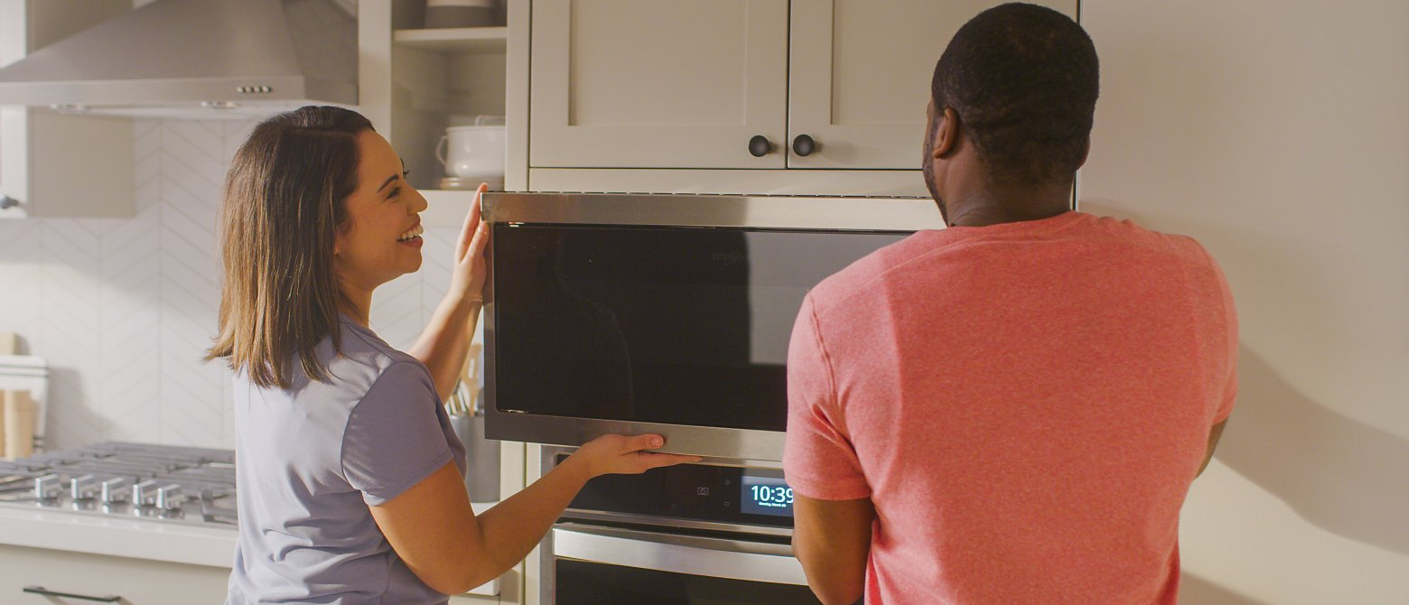 Man and woman installing a microwave