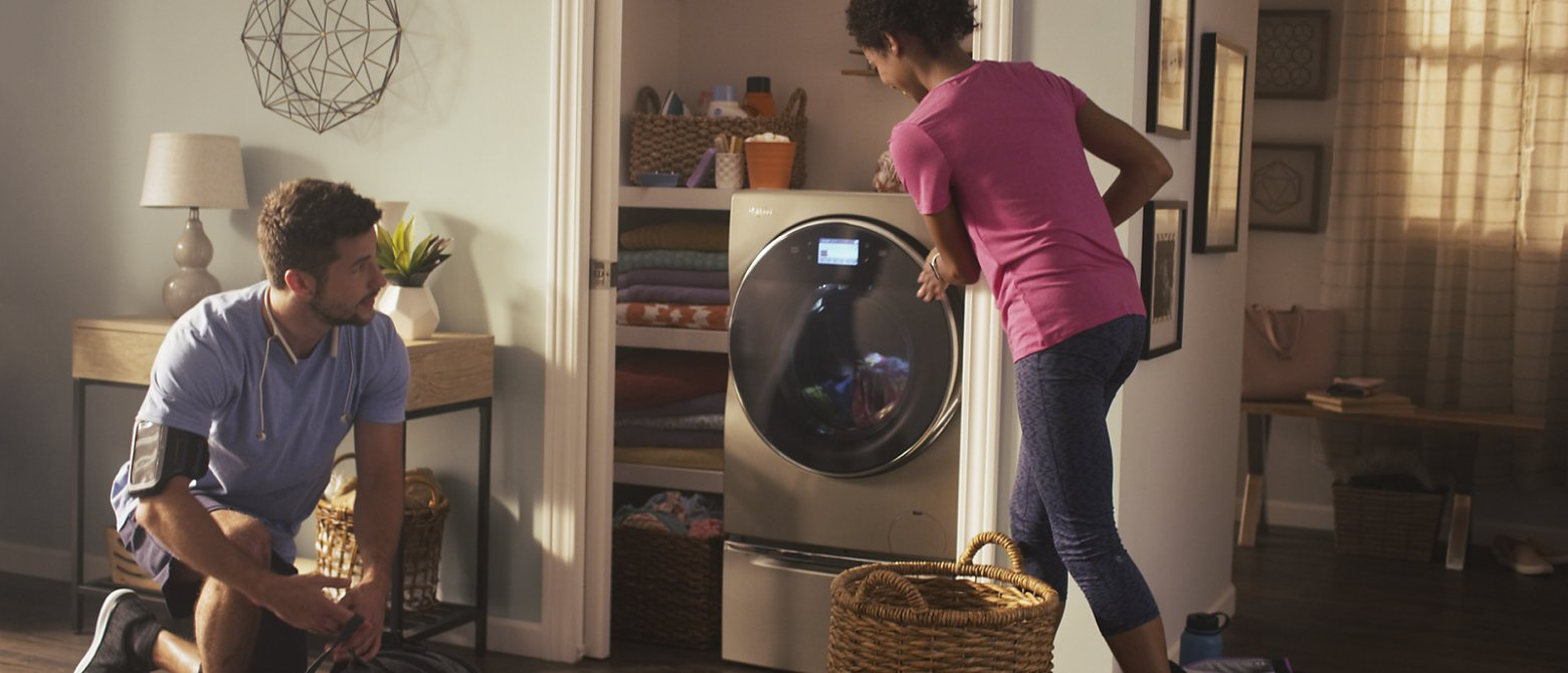 Man and woman in athletic gear loading the washing machine