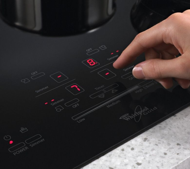 Hand choosing settings on induction cooktop