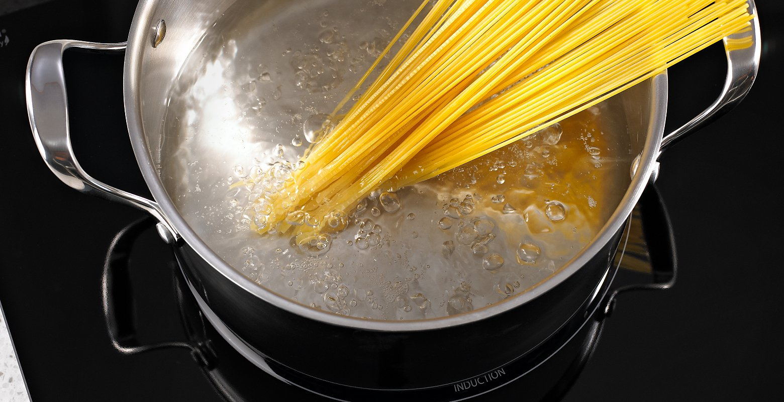 Spaghetti noodles in a pot of boiling water on an induction cooktop