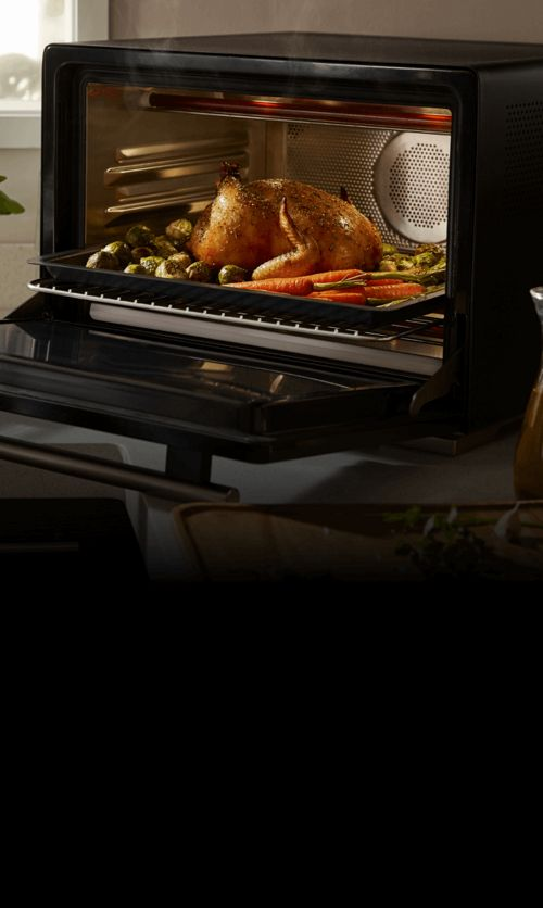 An open WLabs™ Smart Oven on a counter filled with cooked chicken and vegetables.