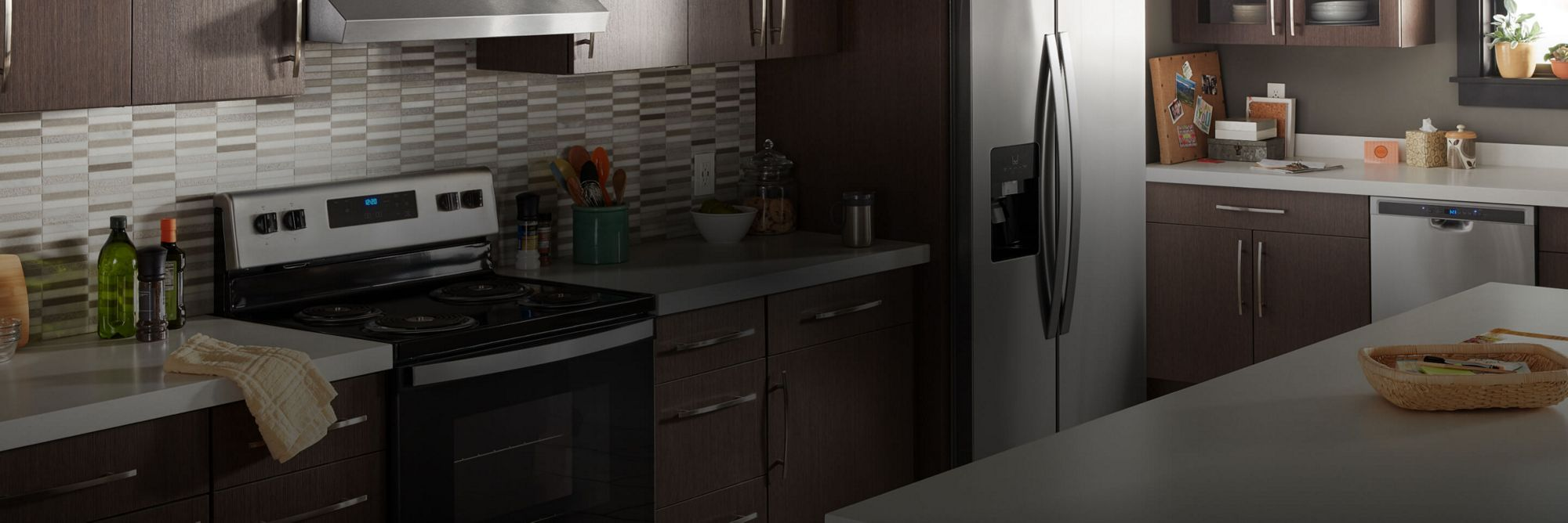 Whirlpool® kitchen suite featuring an electric range and side-by-side refrigerator.