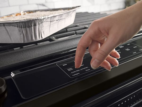 A hand pressing the buttons on a stove the preheat the oven