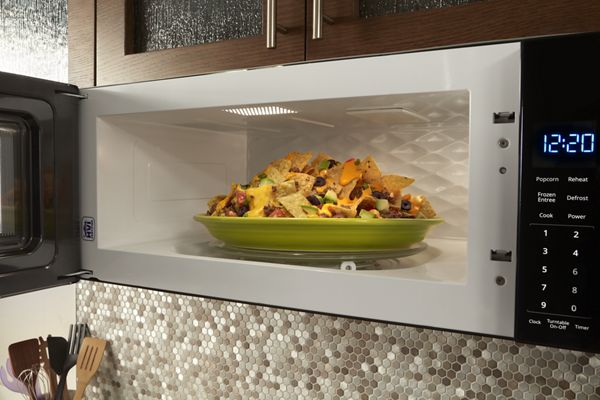 A plate of nachos warming up in the microwave