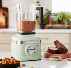 The KitchenAid K400 Blender sitting on a countertop with almonds, cocoa powder.